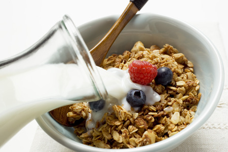 no movement: Pouring milk over crunchy muesli with berries in bowl