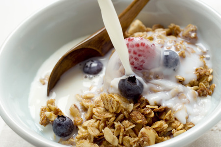 pouring milk: Pouring milk over crunchy muesli with berries LANG_EVOIMAGES