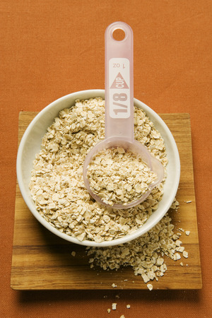 rolled oats: Rolled oats in a bowl with plastic measuring spoon LANG_EVOIMAGES