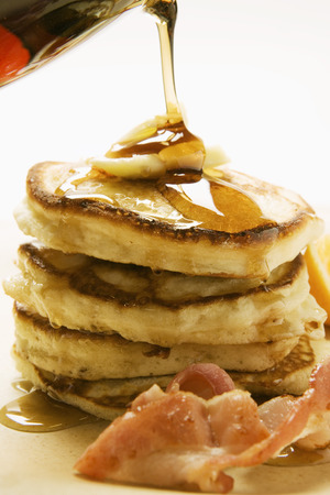 substantial: Pouring maple syrup over pancakes, butter and bacon