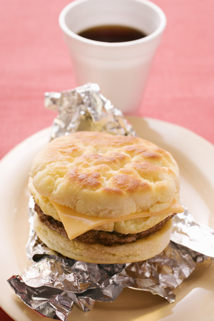 substantial: Cheeseburger with scrambled egg on aluminium foil, coffee cup