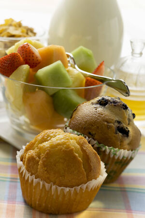 Brunch with muffins, fruit salad, cereal and honey