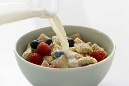 pouring milk: Pouring milk over shredded wheat cereal