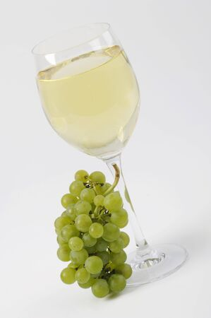 white wine glass: White wine grapes beside full white wine glass LANG_EVOIMAGES