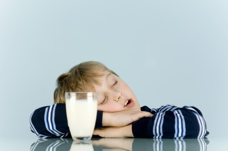 well beings: Boy sitting in front of glass of milk with his eyes closed