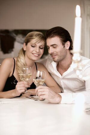 aaa: Young couple clinking glasses of white wine LANG_EVOIMAGES
