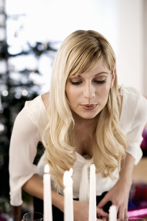 candlelit: Woman blowing out candle LANG_EVOIMAGES