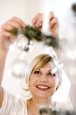 decorating christmas tree: Young woman decorating Christmas tree LANG_EVOIMAGES