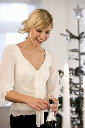 30 to 35 year olds: Young woman opening champagne bottles