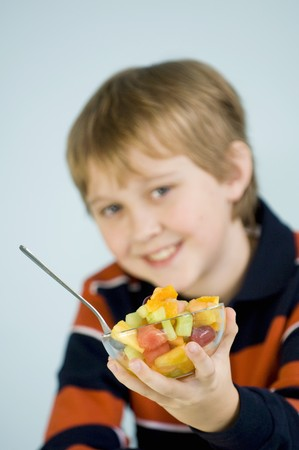 10 to 12 year olds: Boy holding a small bowl of fruit salad LANG_EVOIMAGES