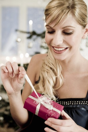 30 to 35 year olds: Woman unwrapping Christmas gift