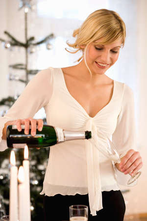 30 to 35 year olds: Young woman pouring champagne LANG_EVOIMAGES