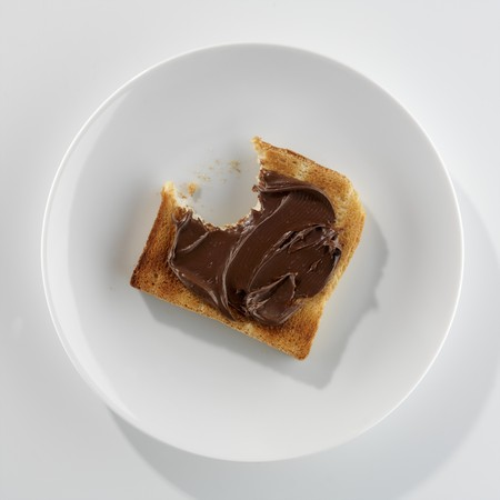 nutella: A slice of toast with Nutella, a bite taken, on a plate