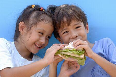 ham sandwich: Two children eating a ham sandwich
