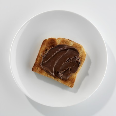 nutella: A slice of toast with Nutella on a plate