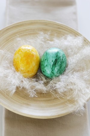 yellowish green: Two coloured Easter eggs with feather in wooden bowl