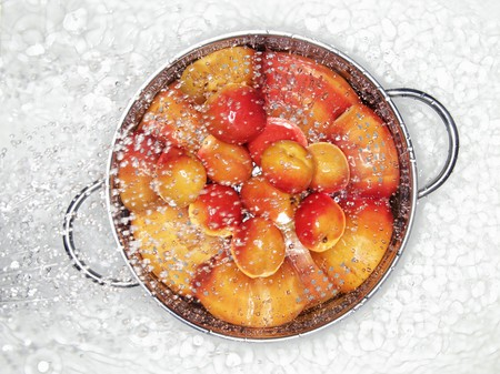 spattering: Apricots in a colander being sprayed with water LANG_EVOIMAGES