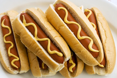 several breads: Six hot dogs with mustard