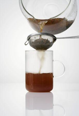 straining: Straining herb tea through a strainer LANG_EVOIMAGES