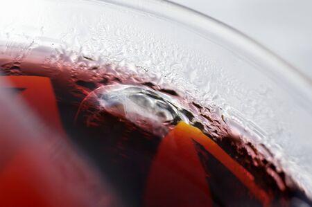 jugo de frutas: Jugo de fruta roja con cubitos de hielo en un vaso
