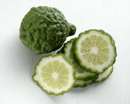 kafir lime: Kaffir limes, one whole and one sliced