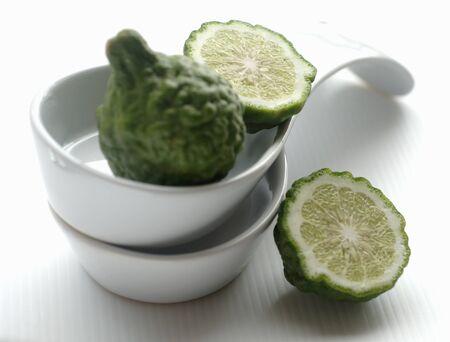 kafir lime: Whole and halved kaffir limes with dishes LANG_EVOIMAGES