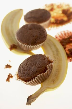 glass topped: Three chocolate banana muffins with halved banana LANG_EVOIMAGES