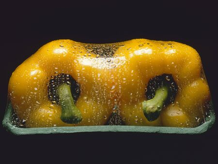 aaa: Two yellow peppers in packaging with drops of water LANG_EVOIMAGES