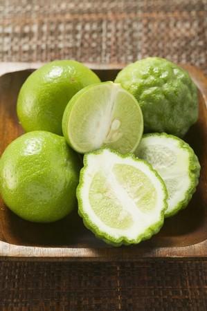 kafir lime: Kaffir limes and limes in wooden bowl LANG_EVOIMAGES