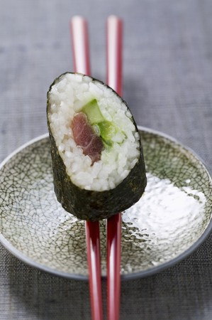 tunafish: A maki sushi with tuna and cucumber on chopsticks LANG_EVOIMAGES