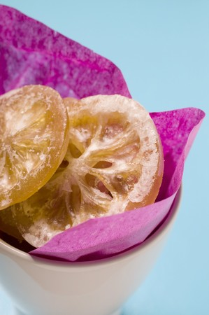 lemon slices: Fette di limone candite in una ciotola con carta viola