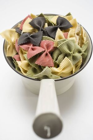 yellowish green: Coloured farfalle in strainer LANG_EVOIMAGES