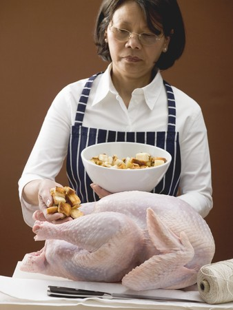 stuffing: Woman stuffing turkey with bread cubes