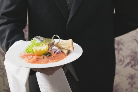 serve one person: Butler serving smoked salmon with toast LANG_EVOIMAGES