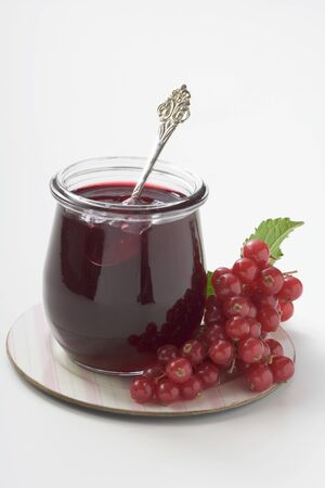 redcurrant: Jar of redcurrant jelly with spoon, redcurrants beside it