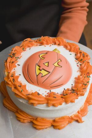 somebody: Hand holding Halloween cake on plate