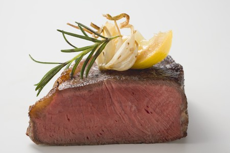 citrus family: Beef steak, showing cut edge, with garlic, rosemary, lemon