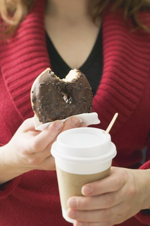 coatings: Woman holding chocolate doughnut with bite taken & cup of coffee