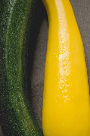 cocozelle: Yellow and green courgettes on brown fabric background LANG_EVOIMAGES
