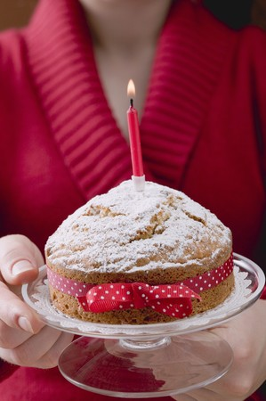 Woman serving birthday cake with bow and candle