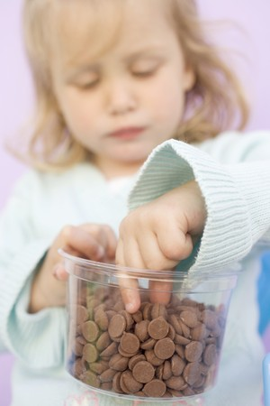 choco chips: Small girl eating chocolate buttons out of plastic tub