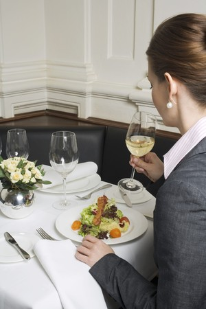 25 to 30 year olds: Woman drinking white wine with salad in restaurant LANG_EVOIMAGES