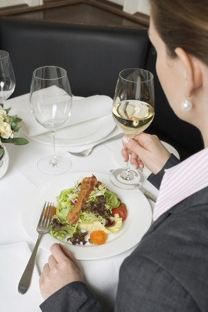 connoisseurs: Woman drinking white wine with salad in restaurant LANG_EVOIMAGES