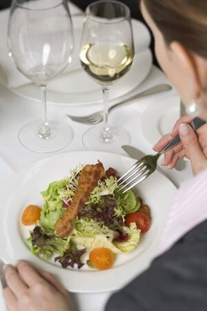 25 to 30 year olds: Woman eating salad in restaurant
