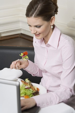 25 to 30 year olds: Woman eating salad while working on laptop in restaurant