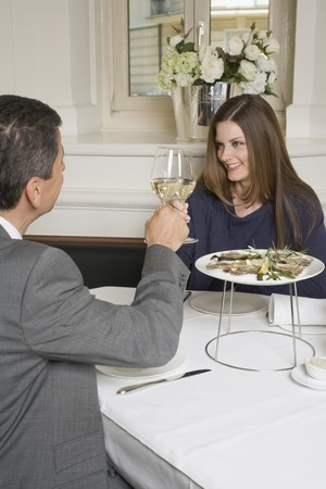 35 to 40 year olds: Couple clinking glasses of white wine in restaurant