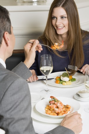 somebody: Man offering woman prawn on fork in restaurant