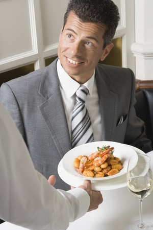 35 to 40 year olds: Waiter serving gnocchi with prawns to man LANG_EVOIMAGES
