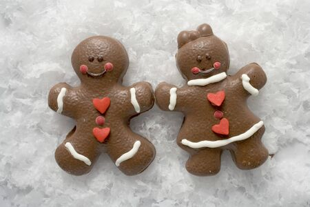 figurative: Two Christmassy chocolate-coated gingerbread people in snow
