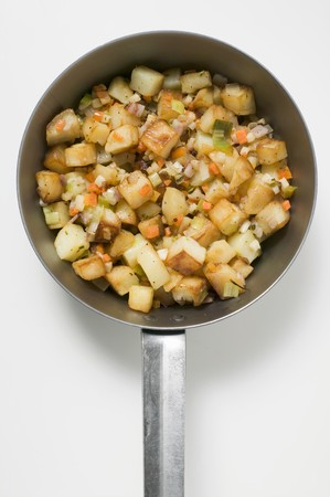 hashbrowns: Fried potatoes with vegetables and bacon in frying pan